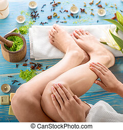 Woman taking spa procedures - Taking care oiling legs in spa...