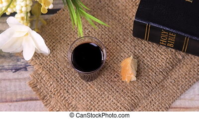 Taking communion concept - the wine and the bread symbols of Jesus Christ blood and body with Holy Bible. Easter Passover and Lord Supper concept. Dolly shot