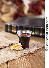 Taking Communion. Cup of glass with red wine, bread and Holy...