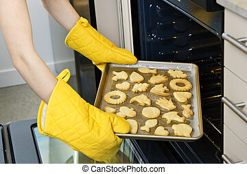 Taking cookies from oven - Taking fresh baked shortbread ...