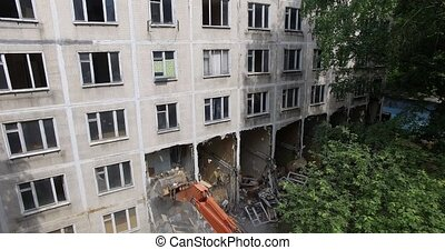 Taking down dilapidated apartment house, aerial view - ...