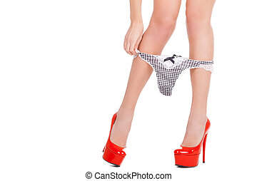 Taking her panties off. Close-up cropped image of woman in red high heeled shoes taking off her panties while standing isolated on white background