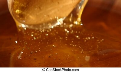 Taking honey by using spoon in wooden bowl, slow motion, close up