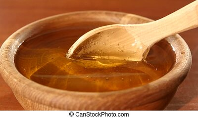 Taking honey by using spoon in wooden bowl