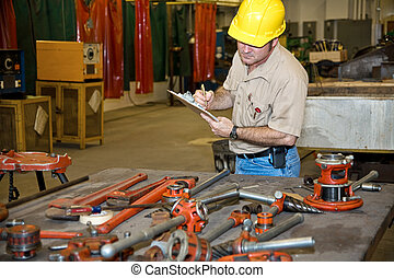 Taking Inventory - Auditor taking inventory of tools in an...