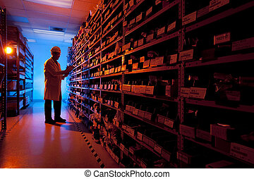 Factory Worker taking inventory in stock room of a manufacturing company back lit by blue and orange light