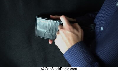 Taking Money Out of a Purse. The man opens a leather purse and pulls out a dollar bill