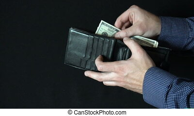 Taking Money Out of a wallet. The man opens a leather wallet...