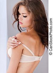 Taking off her bra. Rear view of attractive young woman...