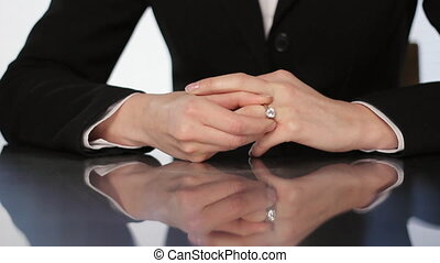 Taking off wedding ring. - A woman takes off her diamond...