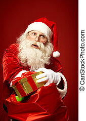Taking out gifts - Portrait of happy Santa Claus taking...