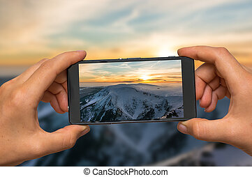 Taking photo of sunset in mountains with mobile phone