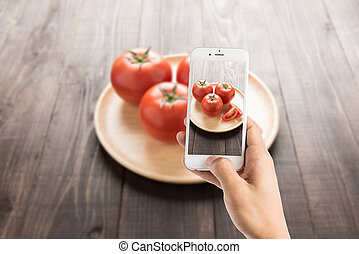 Taking photo of tomatoes on the old wooden table