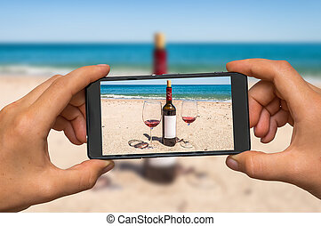 Taking photo of wine and glasses with mobile phone