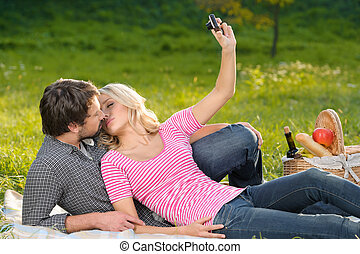 Taking photographs of themselves. Loving young couple taking the photographs of themselves on summer picnic