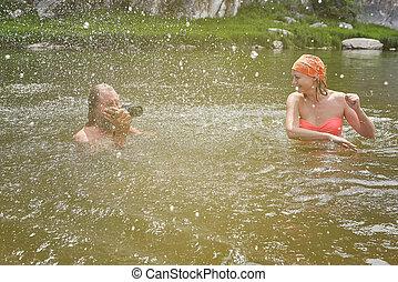 Taking photos and splashing water in river.