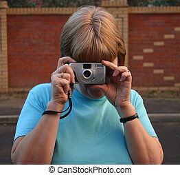 taking photos - female taking photograph with compact point ...
