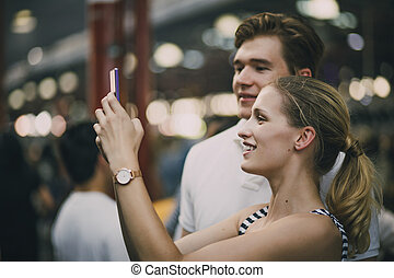 Taking Photos In Queen Victoria Market - Young couple are...