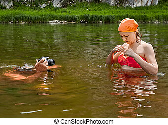 Taking photos of woman in river.