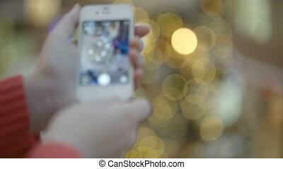 Taking pictures of Christmas tree. - Woman taking pictures...
