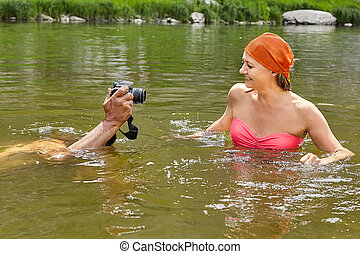 Taking pictures of smiling woman in water.