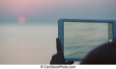 Taking pictures of sunset over sea with touch pad