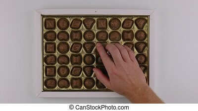 Box of chocolate bonbon candies put on a table and hands taking pieces fast and greedy hoarding
