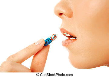 Taking pill - Profile of young woman holding pill by her ...