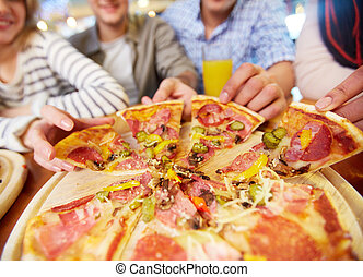 Taking pizza - Image of teenage friends hands taking slices...