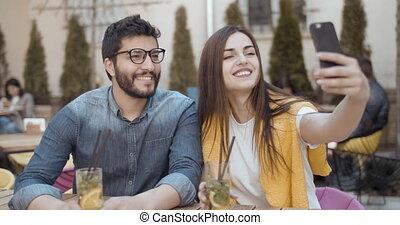 Taking Selfie om Smartphone - Cheerful couple taking selfie...