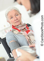 Taking senior woman's blood pressure