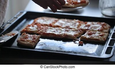 Taking slice of pizza on the baking tray