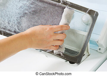 Horizontal photo of female hand taking the lent out from dirty air filter of the dyer machine