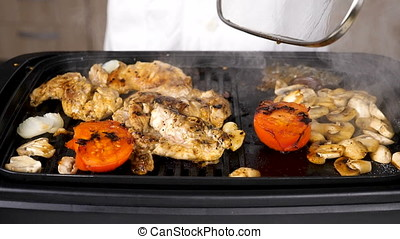 Taking the lid of a grill with meat and mushrooms