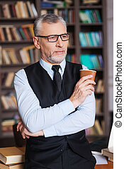 Taking time for a little break. Confident grey hair senior man in formalwear holding coffee cup and looking away while leaning at the table and with bookshelf in the background