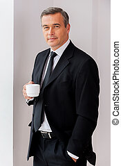 Taking time for coffee break. Confident mature man in formalwear holding coffee cup and looking at camera while standing near the window