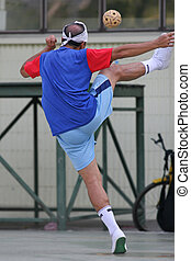 A server volleys the ball over the net in Sepak Takraw (Kick Volleyball), which is a fast-growing and popular sport in Asia