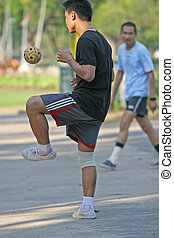 A game of circle takraw using a rattan ball. Players stand in a circle and try to keep the ball airborne as long as possible. The game is popular in Thailand, Malaysia and the Phillipines
