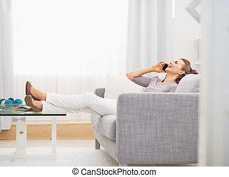 talande, kvinna sitta, soffa, ung, mobiltelefon, medan, lycklig