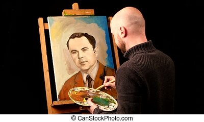 Talanted artist paints a picture, man, of oil paint brush with palette in his hand, on easel, black background,