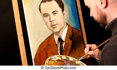 Talanted artist paints a picture, man, of oil paint brush with palette in his hand, on easel