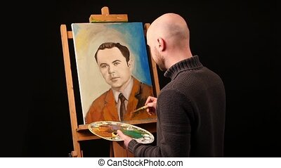 Talanted artist paints a picture, man, of oil paint brush with palette in his hand, on easel, slow motion