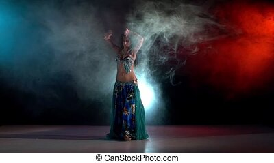 Talanted belly dance movements of young and attractive girl, go on, slow motion, in smoke, black, red, blue