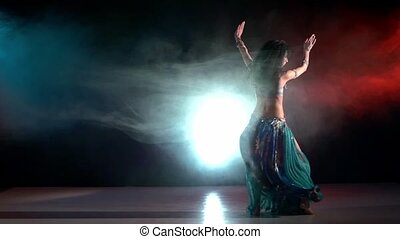 Talanted belly dancer in a blue stage costume dancing in smoke, on red, blue, slow motion