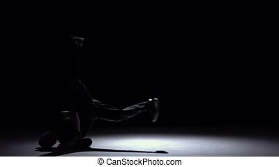 Talanted dancer in dark suit dancing breakdance, on black, shadow, slow motion
