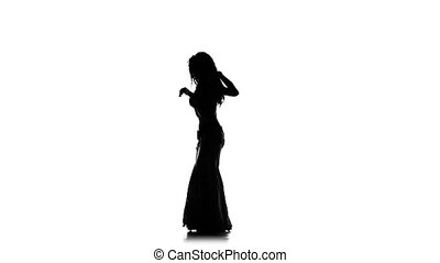 Talanted exotic belly dancer woman, shaking her hips, on white, slow motion, silhouette