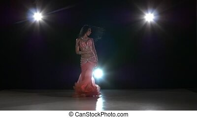 Talanted exotic belly dancer young attractive woman dancing, on black, back light, slow motion