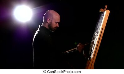 Talanted painter continues drawing a painting by oil paints holding the palette in his hand on black background, back light