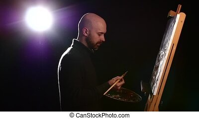 Talanted painter continues drawing a painting by oil paints holding the palette in his hand on black background, back light, slow motion