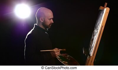 Talanted painter in dark sweater continues drawing a painting by oil paints holding the palette in his hand on black background, back light, slow motion